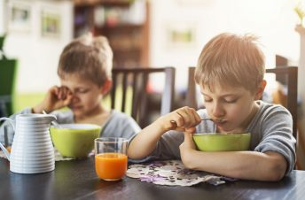 Sleepy kids eating cereal