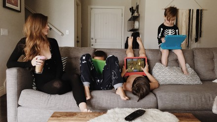 3 kids with iPads on the couch next to their mom enojoying screentime